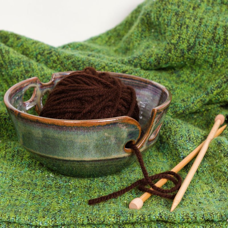 A dark green handmade yarn bowl on a green knitted blanket.