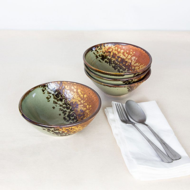 A set of small, green and orange dinnerware bowls sitting next to a fork and spoon on a white napkin.