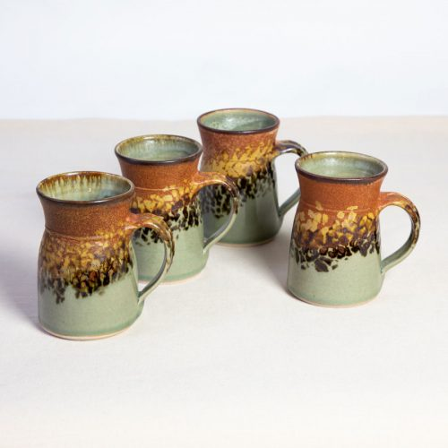 a set of 4 handmade green and orange flare sided mugs on a tablecloth.
