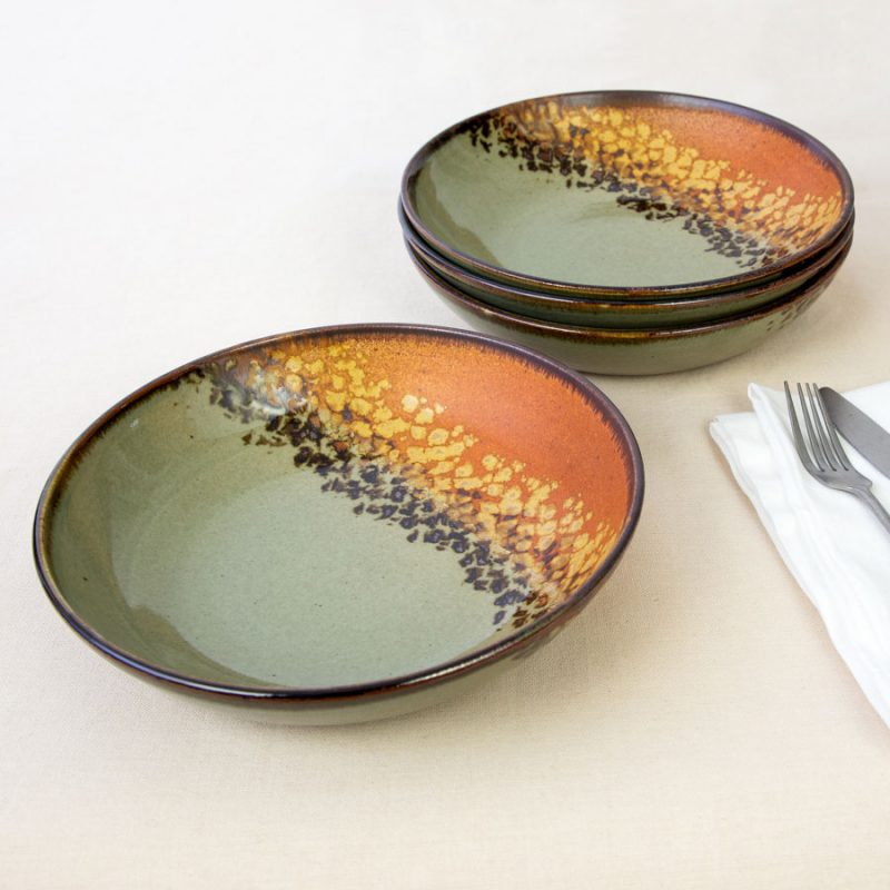 a set of 4 green and orange shallow dinnerware bowls on a tablecloth.