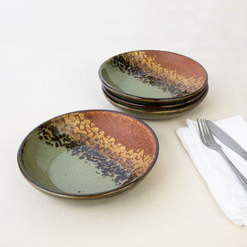 a set of 4 small green and orange shallow handmade bowls on a tablecloth.