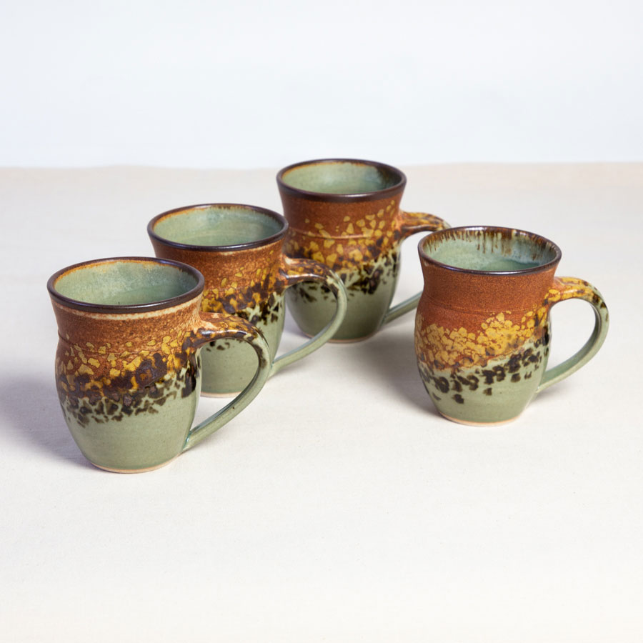 A set of 4 handmade blue and orange round sided mugs on a tablecloth.