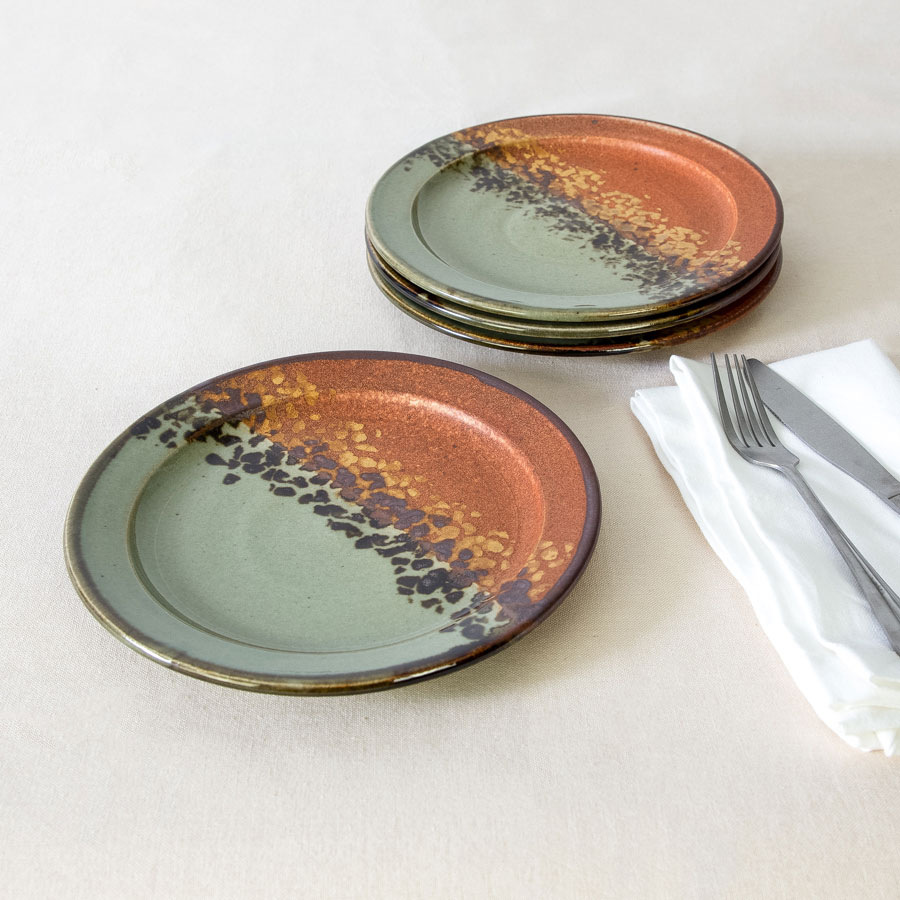 a set of 4 small green and orange handmade dinnerware plates on a tablecloth.