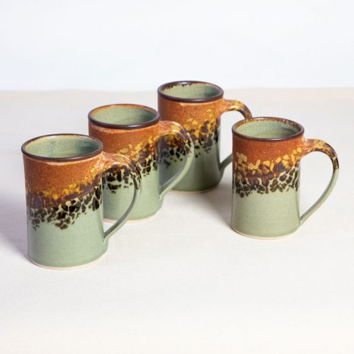 A set of 4 handmade, orange and green straight sided mugs on a tablecloth.