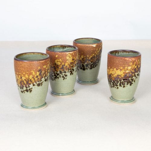 A set of small, green and orange tumblers on a tablecloth.