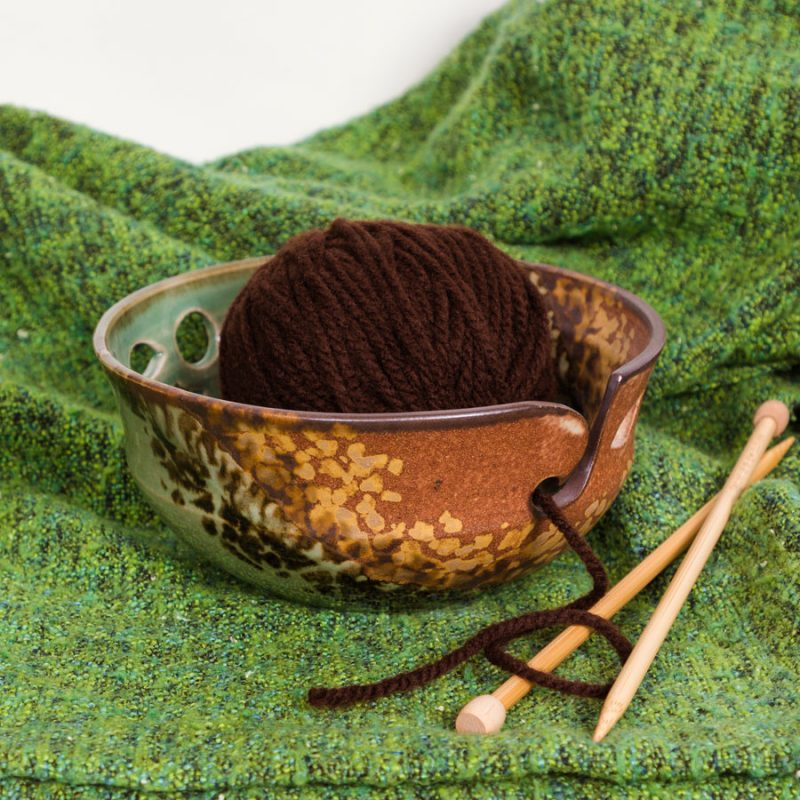 An orange and green handmade yarn bowl on a green knitted blanket.