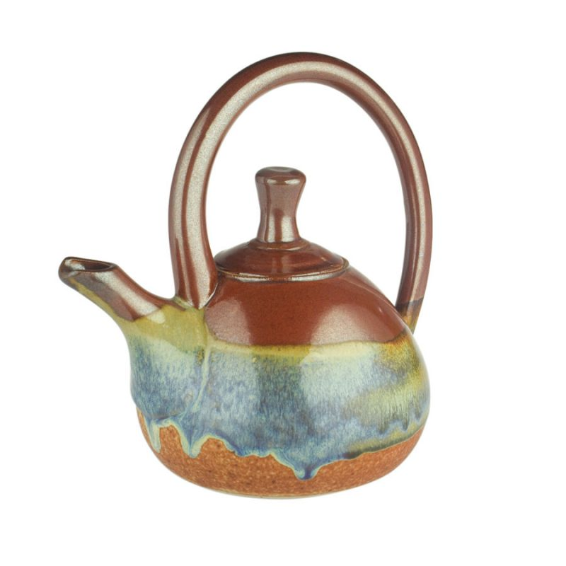 A red and orange teapot with a large looping handle on top and a short spout.