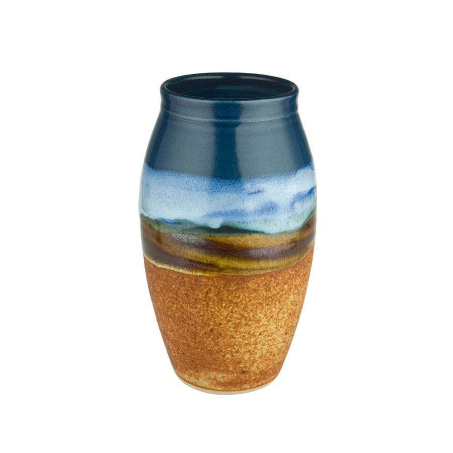 A tall, cylindrical, handmade vase for holding flowers. The pottery is blue on top, and orange on the bottom.