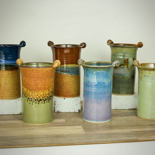6 tall, cylindrical vases for holding wine bottles, each with 2 carrying handles on the rim. Each item is in a different pattern set against a white background.
