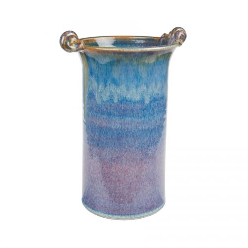 A tall, cylindrical, handmade vase for holding wine bottles, with 2 carrying handles on the rim. The pottery is blue, with a bronze colored rim.