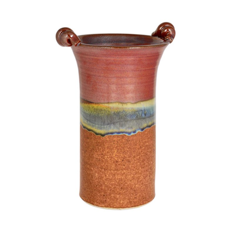 A tall, cylindrical, handmade vase for holding wine bottles, with 2 carrying handles on the rim. The top half of the pottery is red, the bottom half orange.