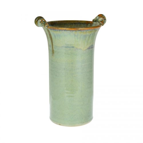 A tall, cylindrical, handmade vase for holding wine bottles, with 2 carrying handles on the rim. The pottery is pale green, with a bronze colored rim.