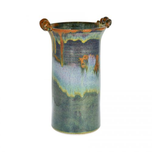 A tall, cylindrical, handmade vase for holding wine bottles, with 2 carrying handles on the rim. The pottery is dark green, with a bronze colored rim.,