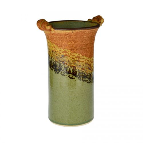 A tall, cylindrical, handmade vase for holding wine bottles, with 2 carrying handles on the rim. The pottery is orange on top, and green on the bottom, with a black and gold animal print across the middle
