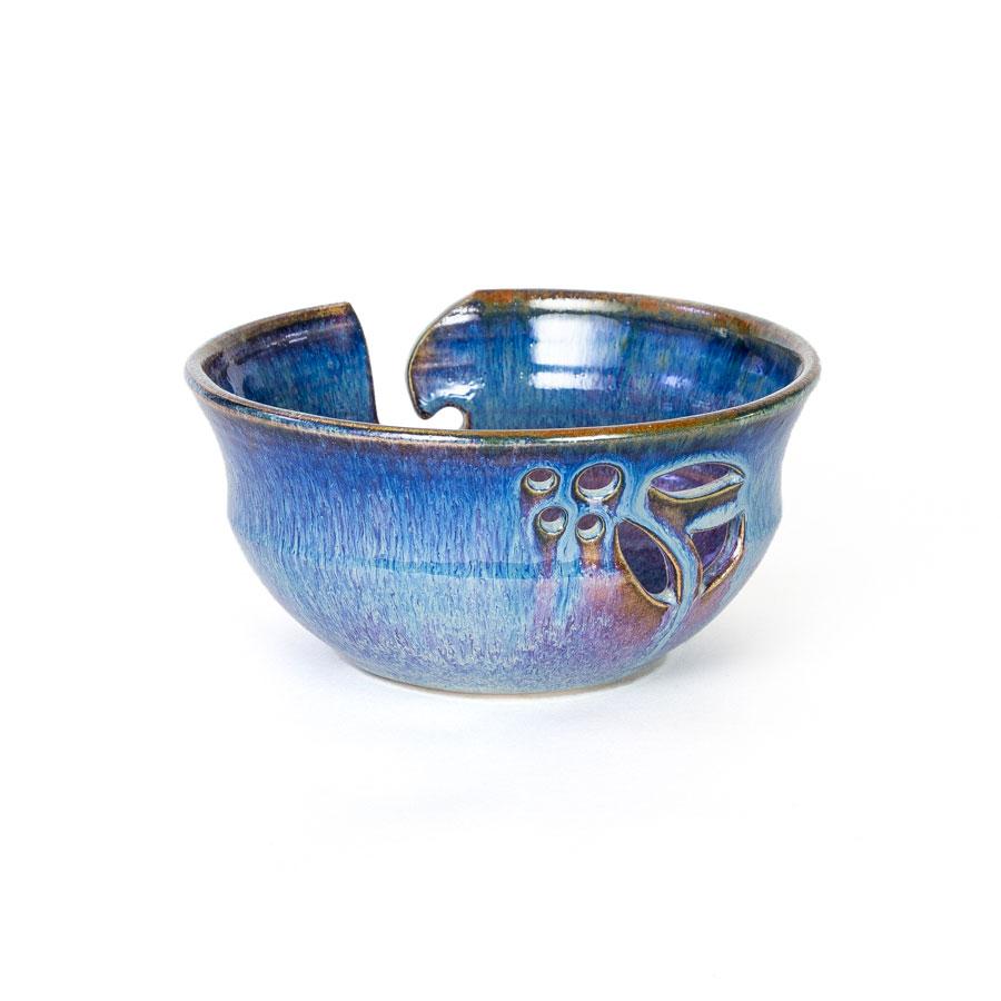 A back view of a handmade blue ceramic yarn bowl.