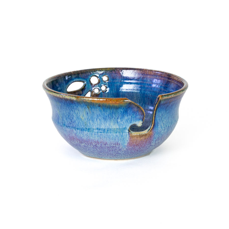 A frontal view of a handmade blue ceramic yarn bowl.