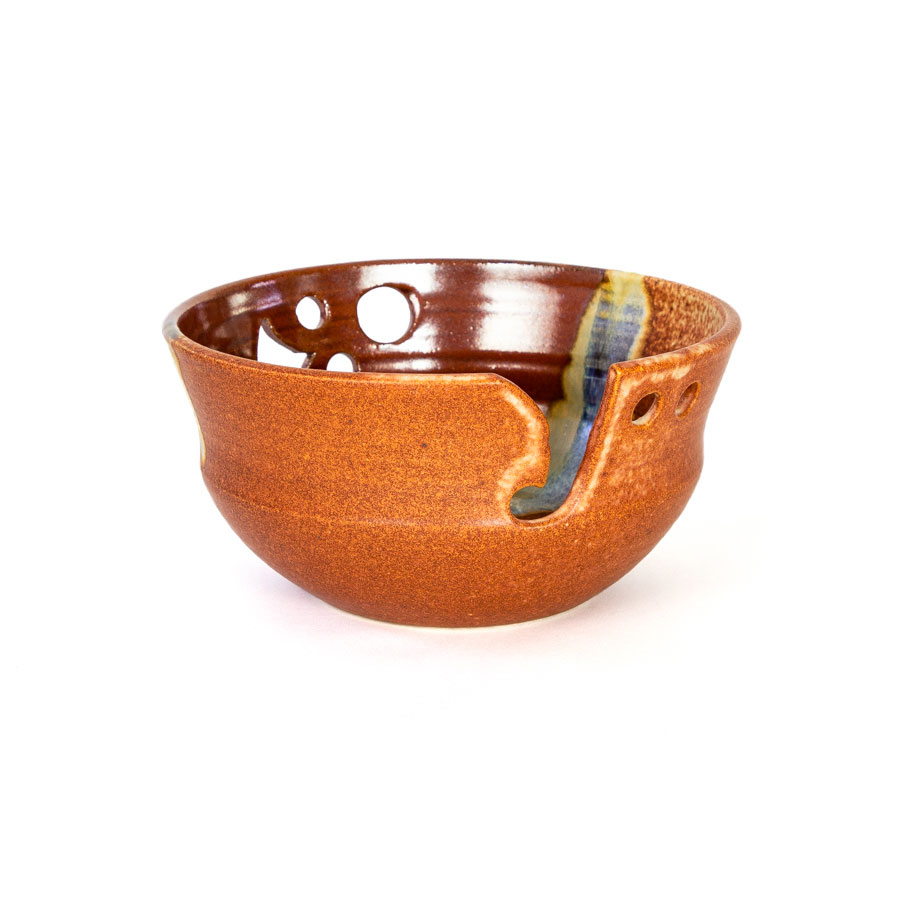 A frontal view of a handmade red and orange ceramic yarn bowl.