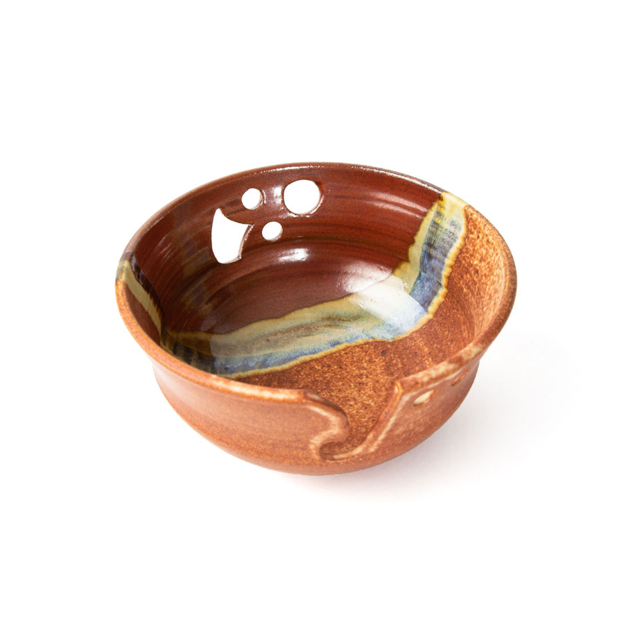 a top view of a red and orange handmade ceramic yarn bowl.