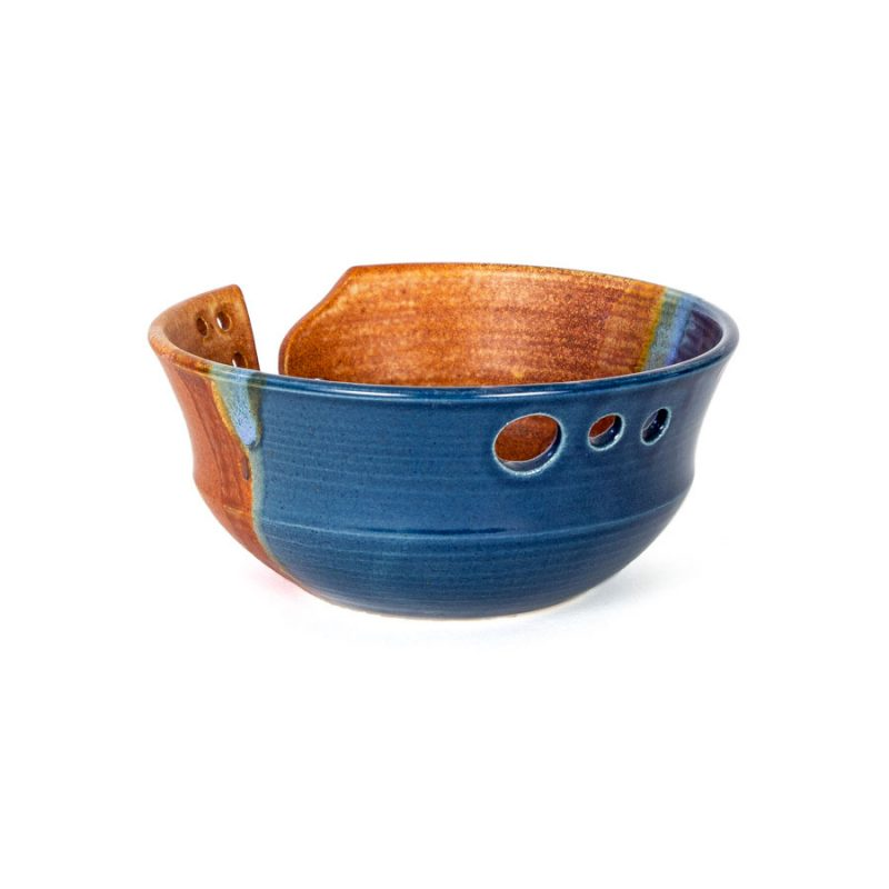 A back view of a handmade blue and orange ceramic yarn bowl.