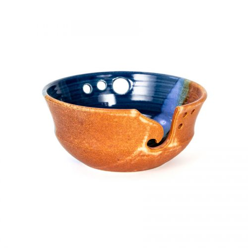 A frontal view of a handmade blue and orange ceramic yarn bowl.