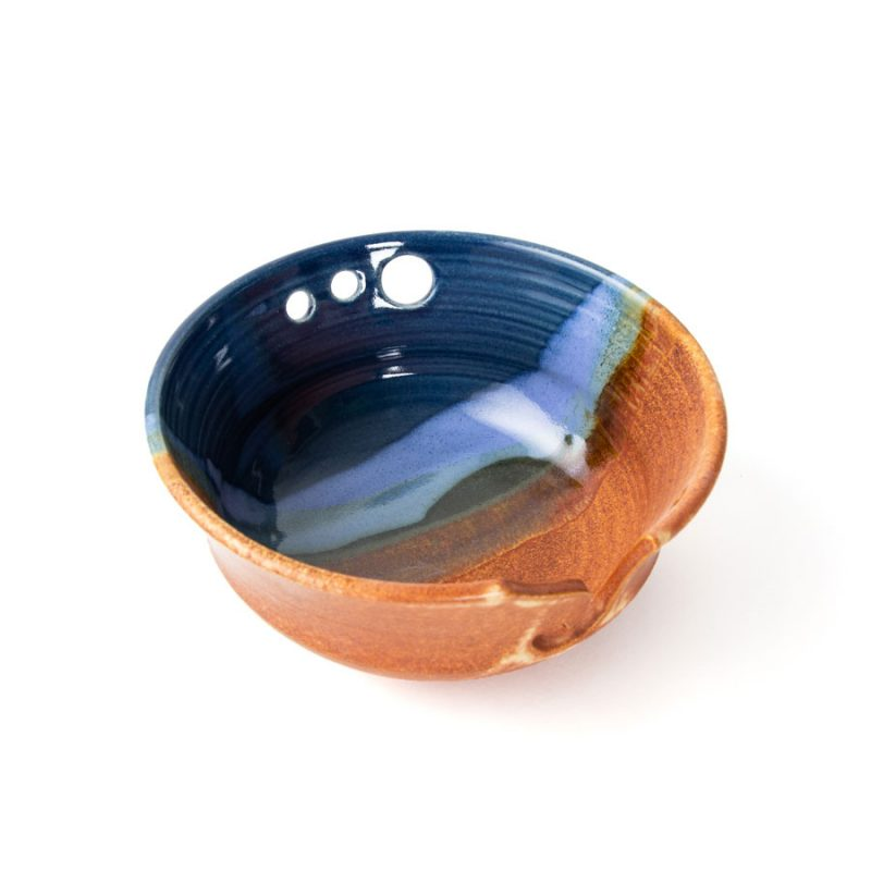 a top view of a blue and orange handmade ceramic yarn bowl.