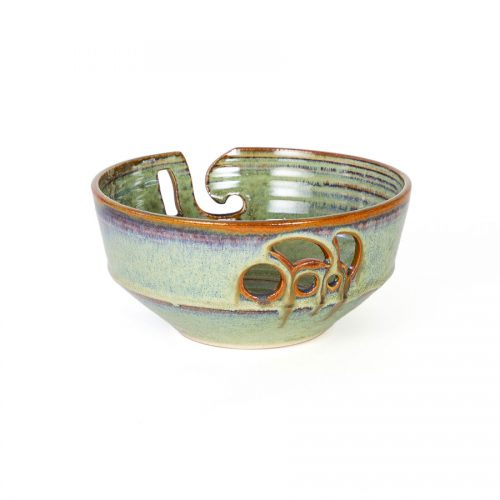 A back view of a handmade pale green ceramic yarn bowl.