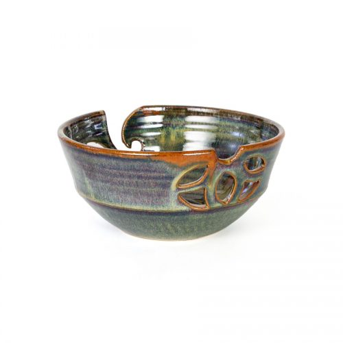 A back view of a handmade dark green ceramic yarn bowl.