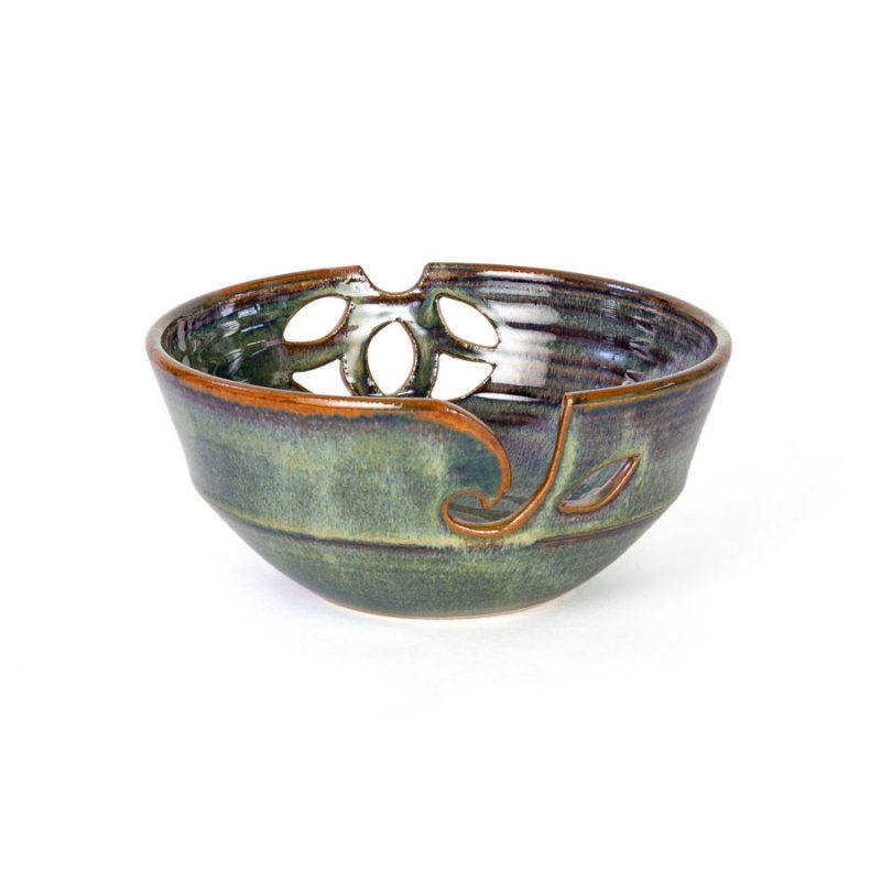A frontal view of a handmade dark green ceramic yarn bowl.