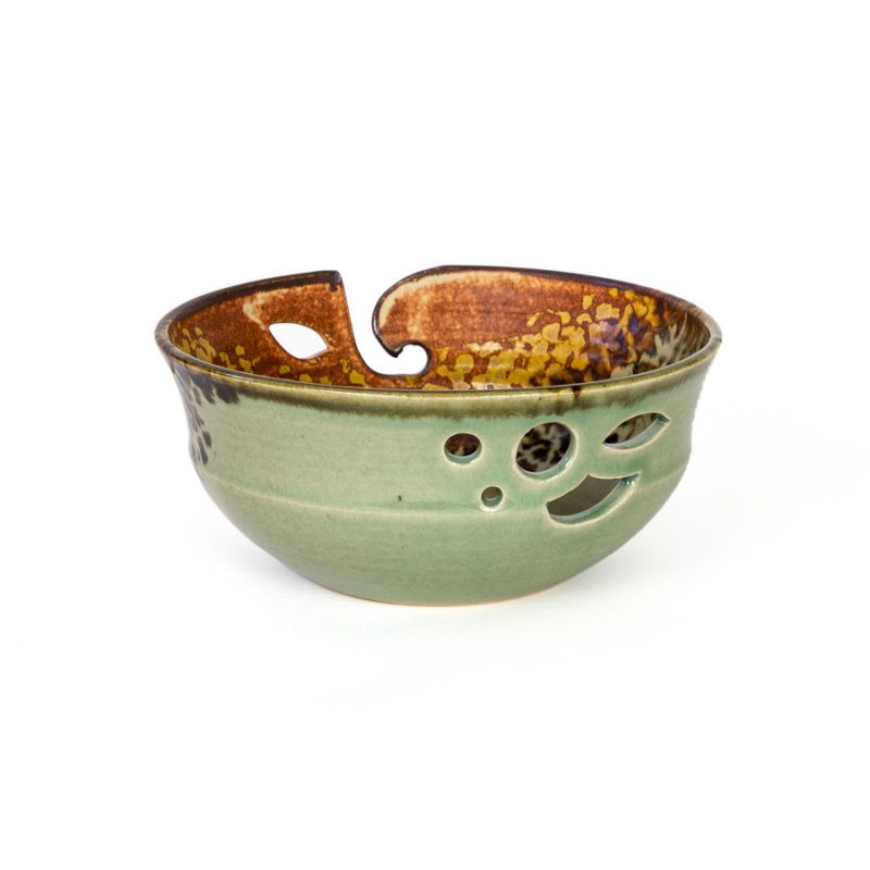 A back view of a handmade green and orange ceramic yarn bowl.