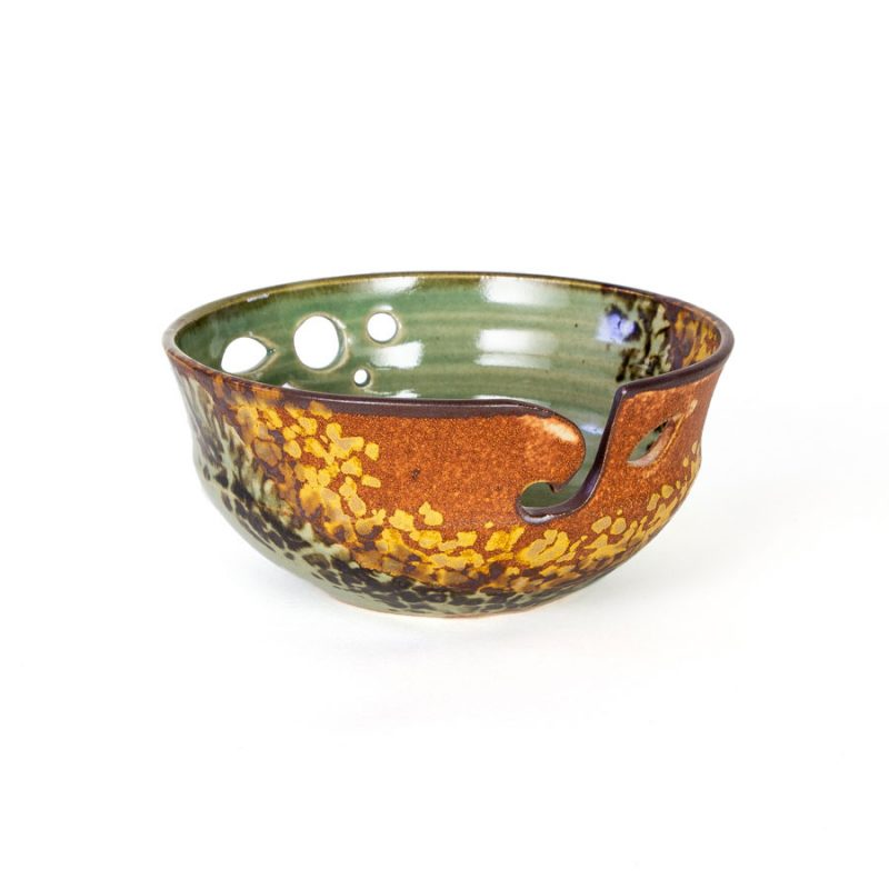 A frontal view of a handmade green and orange ceramic yarn bowl.