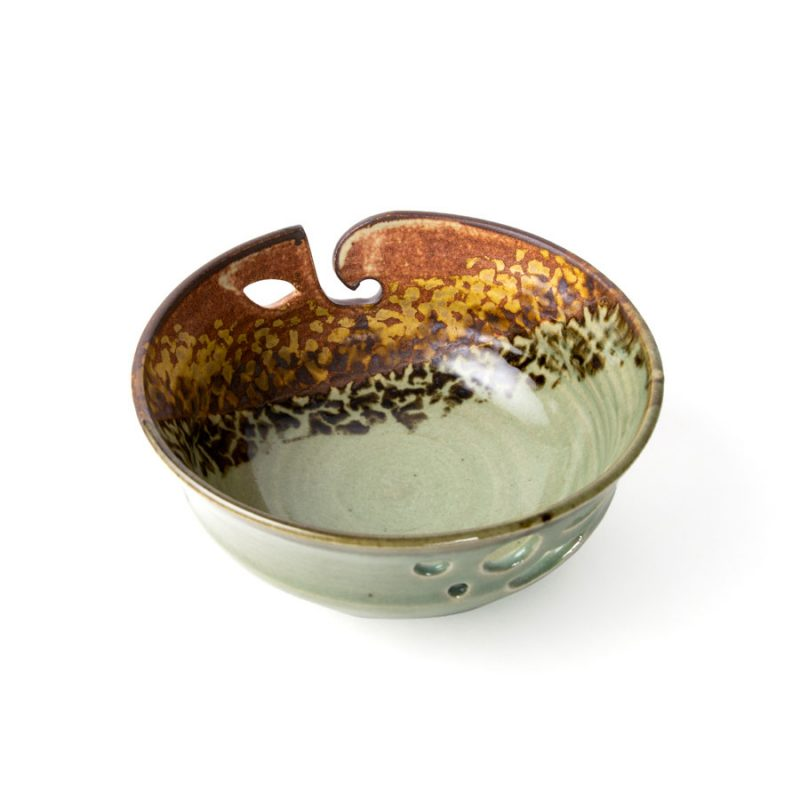 a top view of a green and orange handmade ceramic yarn bowl.